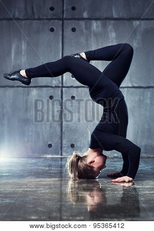 Strong woman gymnast in black clothing stretching upside down on wall background.