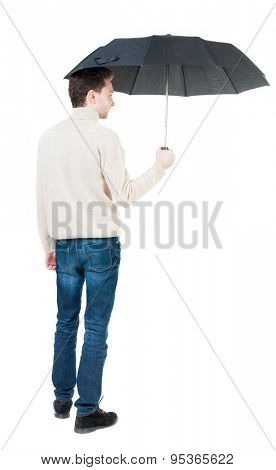 Back view of man in jeans under an umbrella. Standing young guy.   Isolated over white background. A guy in a white warm sweater hiding from the rain under an umbrella, and someone...