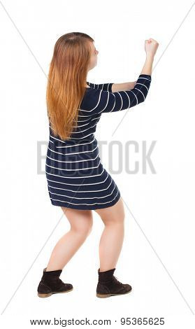 back view of standing woman pulling a rope from the top or cling to something.  Rear view people collection.    Isolated over white background. girl in dark blue dress pulling a rope from the top.