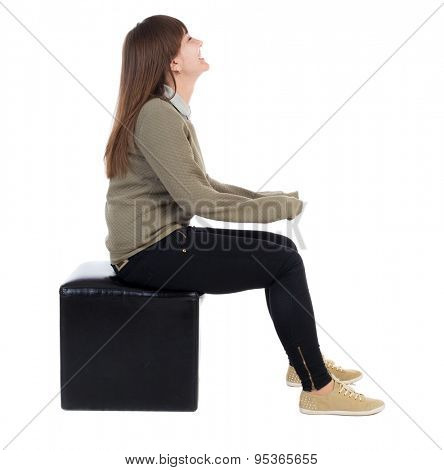 back view of young beautiful  woman sitting.  girl  watching. Rear view people collection.  backside view of person.  Isolated over white background. girl is sitting on a leather ottoman and smiling.