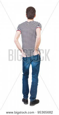 Back view of man in jeans. Standing young guy. Rear view people collection.  backside view of person.  Isolated over white background. A guy in a T-shirt is his hands in the back pockets of jeans.