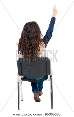 back view of young beautiful  woman sitting on chair and pointing.  girl  watching. Rear view people collection.  Girl in sleeveless sheep sits on a chair and looking ahead.
