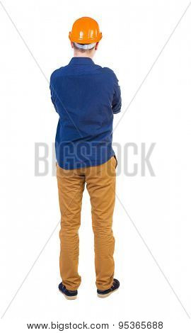 Backview an engineer in construction helmet stands. Standing young guy. Rear view people collection.   Isolated over white background. young engineer standing with his arms crossed and evaluates work.