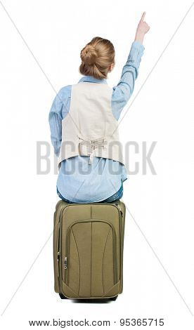 back view of woman sits on a suitcase and pointing.  backside view of person.  Rear view people collection.  Girl in a blue shirt and tank top sitting on a suitcase and shows up.