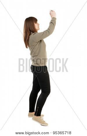 Back view of woman photographing.   girl photographer in jeans. Rear view people collection.  backside view of person.  A girl in a gray sweater on a small camera photographing something in the sky.