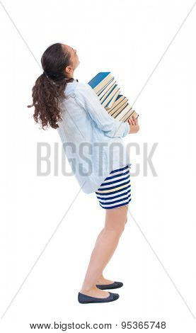 A girl carries a heavy pile of books. back view. Rear view people collection.  backside view of person.   African-American woman in denim jacket carries a pile of books and looking up.