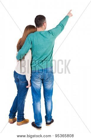 young couple pointing at wal Back view  (woman and man). Rear view people collection.  backside view of person.  I. Man and woman embracing each other to point the finger somewhere in the sky.