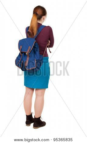 Back view of  woman with backpack looking up. Standing young girl. Rear view people collection.  girl in a blue skirt and a burgundy sweater with a blue backpack standing arms folded.