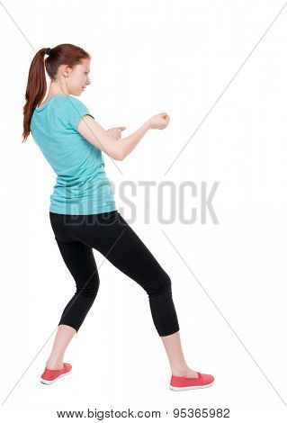 back view of standing woman pulling a rope from the top or cling to something.  Rear view people collection.   Isolated over white background. Sport girl in black tights pulled the right string.