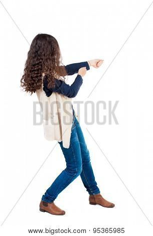 back view of standing woman pulling a rope from the top or cling to something.  Rear view people collection.  Isolated over white background. Girl in sheepskin jerkin pulls the rope on the right ..