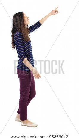 back view walking  woman. beautiful redhead girl pointing.  backside view of person. solated over white background. Curly girl in red pants is right and shows a finger of his right hand at something