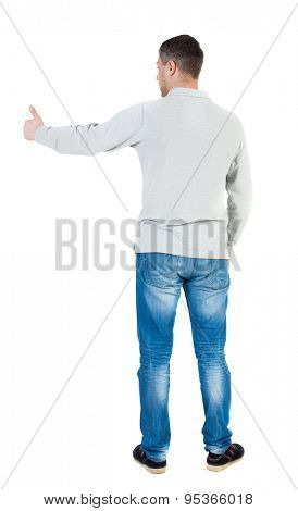 Back view of  man in shirt shows thumbs up.   Rear view people collection.  backside view of person.  Isolated over white background.  The guy who shows a sign to the left...