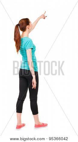 Back view pointing woman in sportswear. beautiful girl. Rear view people collection.  backside view of person. Isolated over white background. Sport girl stands with his right hand pointing upwards
