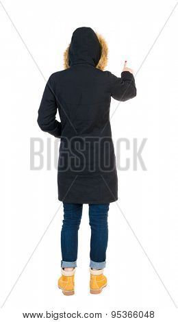 Back view of  pointing young women in parka. Young girl gesture. Rear view people collection.   The tall girl in a black warm jacket with a hood placed over the head presses his forefinger.
