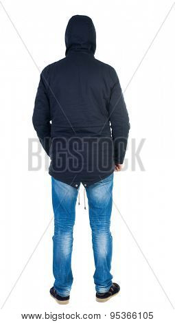Back view of handsome man in winter jacket  looking up.   Standing young guy in parka.   Isolated over white background. Man in warm jacket hood pulled on his head standing and looking.