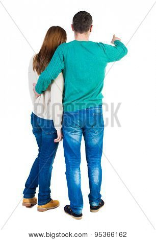 young couple pointing at wal Back view  (woman and man). Rear view people collection.  backside view of person.   The guy in the green jacket holding the girl shows her something interesting ahead.