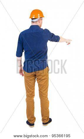 Back view of  pointing young men in  shirt and helmet. Young guy  gesture. Rear view people collection.   Isolated over white background. Young engineer in a blue shirt points to the work front
