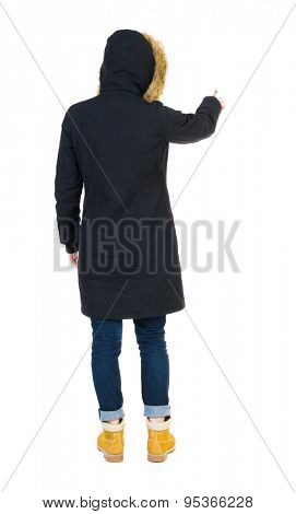Back view of  pointing young women in parka. Young girl gesture. Rear view people collection.  Isolated over white background. The tall girl in a black jacket with warm finger presses the button.
