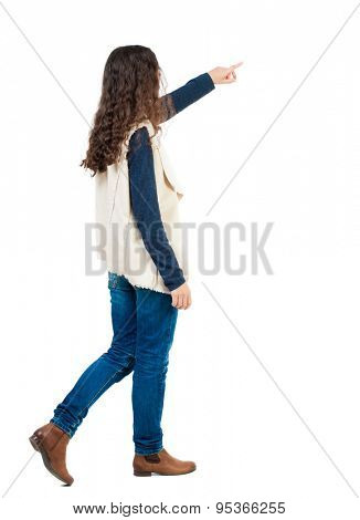 back view of walking  woman. beautiful redhead girl pointing.  backside view of person.  Rear view people collection. Isolated over white background. Girl in sheepskin jerkin goes and shows thumb.