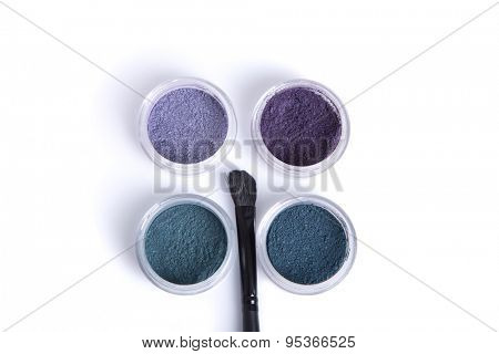 Top view of jars with eye shadows, and makeup brush, isolated on white background