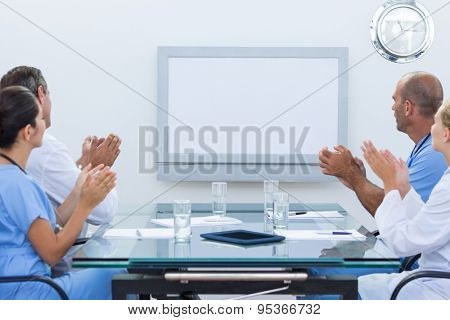 Team of doctor applauding during meeting in medical office