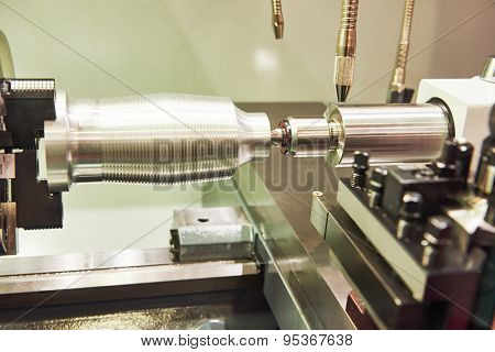 metalworking  industry: cutting steel metal shaft processing on lathe machine in workshop. Selective focus on tool