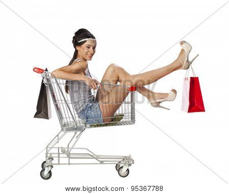 Happy young beautiful brunette woman sits in an empty shopping cart with a red bagisolated on white background