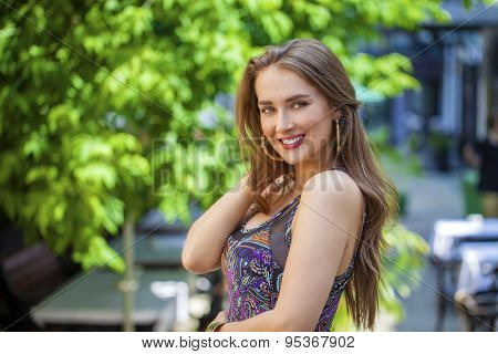 Portrait close up of young beautiful woman, on background summer street