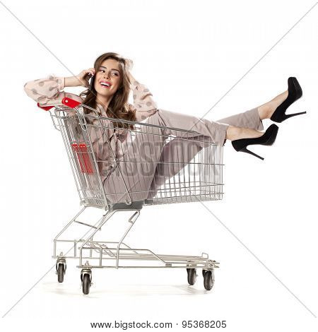 Young beautiful brunette girl talking on a cell phone while sitting in an empty shopping trolley, isolated on white background