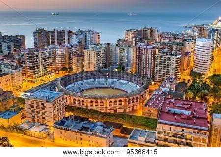 Malaga, Spain cityscape and bullring at dawn.