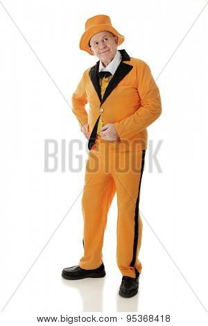 Full length image of a standing senior adult man looking up and off to the side in his orange and black tuxedo and hat.  On a white background.
