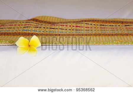 Bed with white sheet, decorated with plumeria flower
