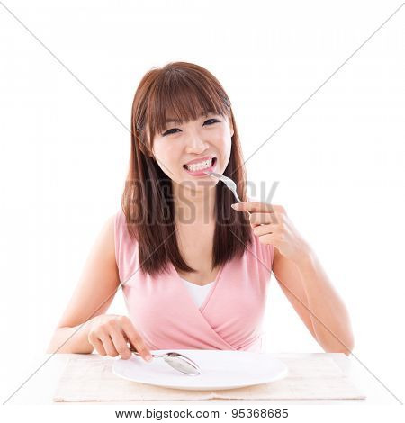 Asian girl eating food with fork and spoon, empty plate ready for food. Young woman living lifestyle.