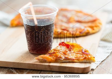 fast food, italian kitchen and eating concept - close up of pizza with cup of coca cola drink on wooden table