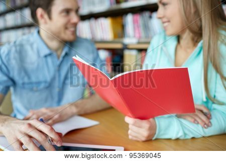 people, learning, communication, education and school concept - close up of happy students with notebooks talking in library