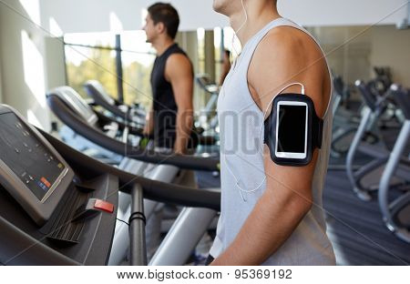 sport, fitness, lifestyle, technology and people concept - man with smartphone and earphones exercising and listening to music on treadmill in gym