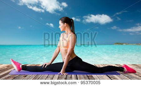 fitness, sport, exercising, stretching and people concept - smiling woman doing splits on mat over sea and wooden berth at resort background