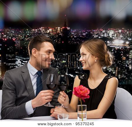 restaurant, couple and holiday concept - smiling young couple with glasses of red wine looking at each other at restaurant