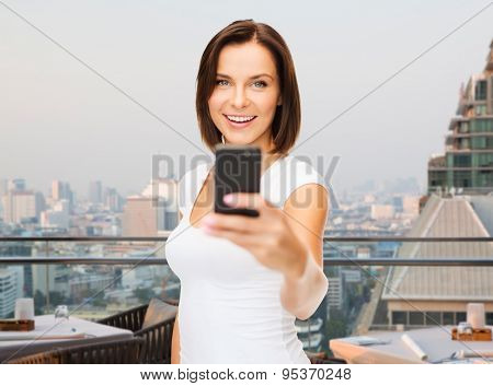 people, technology, tourism and travel concept - young woman taking selfie with smartphone over singapore city background