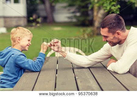 family, happiness, generation, home and people concept - happy father and son doing arm wrestling outdoors