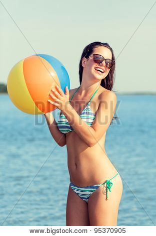 sea, summer vacation, holidays, sport and people concept - smiling teenage girl in sunglasses with inflatable ball on beach
