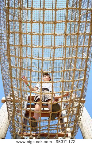 The boy inside the cable cell in playground, bottom view