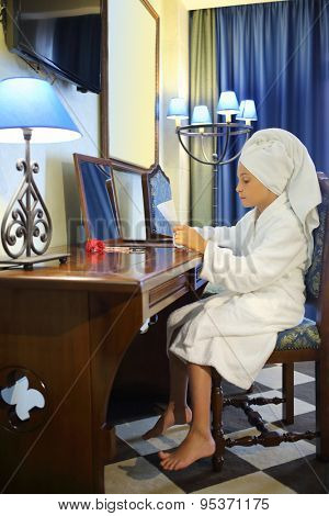 Girl in a white robe and towel on head sitting at a dressing table with a sheet of paper in hands