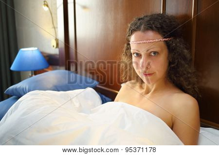 Portrait of beautiful woman with curly hair under a white blanket in the bed
