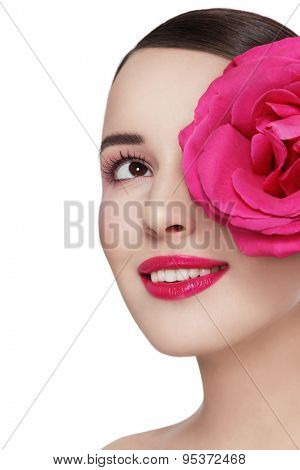 Young beautiful healthy happy smiling woman with fancy pink rose looking upwards over white background, copy space