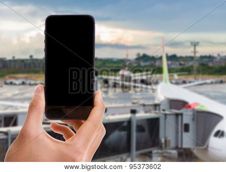 Hand holding mobile smart phone with black screen on airport background