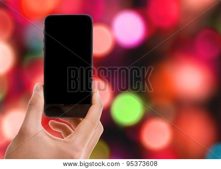 Hand holding mobile smart phone with black screen on bokeh background