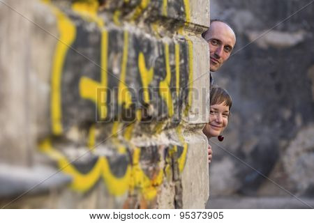 Couple, happy young family. A man and a woman peering mischievously from the corner of the house.