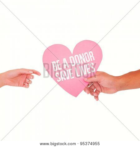 Couple passing a paper heart against be a donor save lives