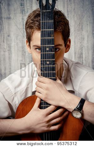 Romantic young man playing an acoustic guitar.